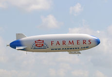Large airship in flight. Fort Lauderdale, USA - May 20, 2011: Airship Eurike visits South Florida on a nationwide tour. the zeppelin bears the name of Farmers Royalty Free Stock Photos