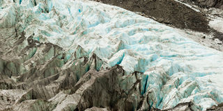 Climate change, melting glacier ice with crevasses. Large alpine glacier icefield melting rapidly due to global warming on its slow flow downwards forming a maze Royalty Free Stock Photography