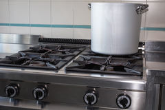 Large aluminum pot over the stove's gas industrial kitchen Royalty Free Stock Images
