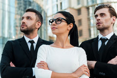 Large ambitions open new horizons. Low angle view of three confident business people keeping arms crossed and looking away while standing outdoors stock photos