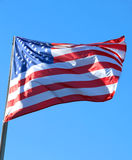 Large American flag flying high in the blue sky Stock Images