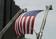 An Large American Flag hanging between Firetruck Ladders Royalty Free Stock Photos