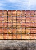 High stacks of orange bricks in storage and ready for shipping to builders under a blue sky and on black asphalt stock image