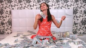 Large amount of money falls on a woman white bed. The girl enjoys a lot of money. slow motion. Huge wealth of money, top. View stock footage
