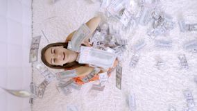 Large amount of money falls on a woman white bed. The girl enjoys a lot of money. slow motion. Huge wealth of money, top. View stock video footage