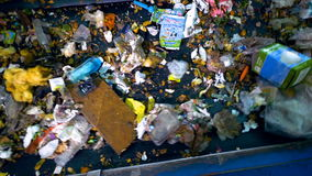 A large amount of trash moving on a waste conveyor. Conveyor transporting a large amount of trash at waste processing plant stock footage