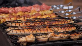 Large amount of unhealthy fatty junk food cooking on grills at street festival. Stock footage stock video