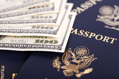 Cash & Passports. A large amount of 100 US dollar money notes on top of a stack of American and German passports. Shallow depth of field Royalty Free Stock Images