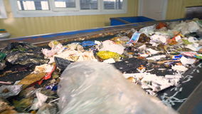 A large amount of waste moving on a waste conveyor. Conveyor transporting a large amount of trash at waste processing plant stock video