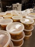 Large amounts of cooked food in plastic containers, stew pot in background royalty free stock photos