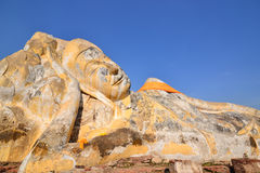 Large ancient reclining Buddha. Large reclining Buddha and clear blue sky Royalty Free Stock Image