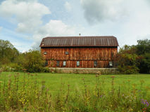 Large antique cedar wood barn with stone foundation centered in green field. Stock Images