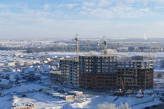 Large apartment buildings construction in new district among rural houses, urbanisation in action. Winter season. Stock Image