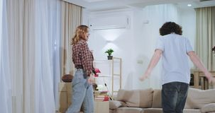 In a large apartment a very attractive and charismatic couple dacing and have a funny moments together after a hard. Moving day in a new house they are very stock video footage