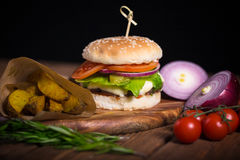 Large appetizing burger with beef, potatoes and cheese on a wooden surface. royalty free stock photography