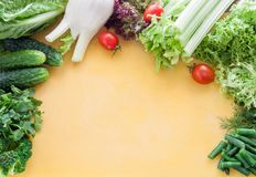 Large assortment of greens, lettuce and vegetables on a yellow board top view. Place for inscription stock photo