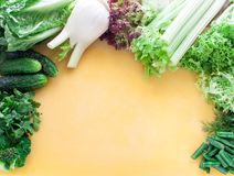 Large assortment of greens, lettuce and vegetables on a yellow board top view stock photo