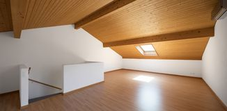 Large attic with wooden floors and exposed beams stock photography