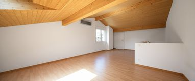 Large attic with wooden floors and exposed beams. White walls, perfect for copy-space royalty free stock photography