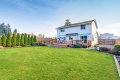 Large back yard with lots of grass and deck. Stock Photography