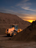 Large Backhoe and Top soil piles at sunset sunrise Stock Photo