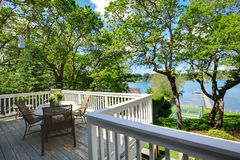 Large balcony home exterior with table and chairs, lake view. Stock Photos