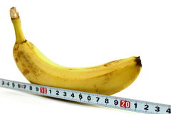 Large banana and measuring tape on white Royalty Free Stock Images