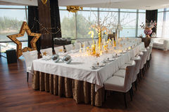 Large banquet table fine restaurant with windows. Large table with cutlery, decorated for a wedding, birthday or party. Large windows, brown floor, white Royalty Free Stock Images