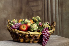 Basket of Fruit Still Life. A large basket of assorted fruits including grapes, avocados and apples. (Still Life Stock Photo