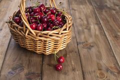 A large basket of ripe cherries. Delicious and sweet berries. Wooden background, free space for text. Retro style. Copy space. royalty free stock images