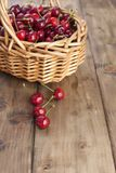 A large basket of ripe cherries. Delicious and sweet berries. Wooden background, free space for text. Retro style. Copy space. stock images