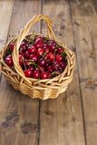 A large basket of ripe cherries. Delicious and sweet berries. Wooden background, free space for text. Retro style. Copy space. stock photography