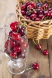 A large basket of ripe cherries and scattered berries on a table and in a glass. Wooden background, free space for text. Retro royalty free stock image