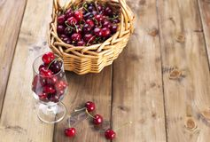A large basket of ripe cherries and scattered berries on a table and in a glass. Wooden background, free space for text. Retro stock images