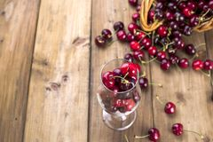 A large basket of ripe cherries and scattered berries on a table and in a glass. Wooden background, free space for text. Retro stock photography