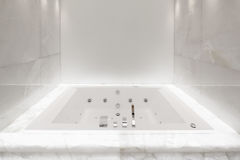 Large bath tub in the bathroom lit marble, nobody Royalty Free Stock Photo