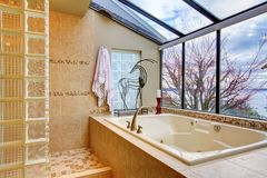 Large bath tub with window wall with water view. Large tub with glass wall and water view near shower stock photo