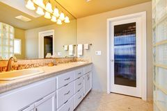 Large bathroom with white cabinets Stock Images