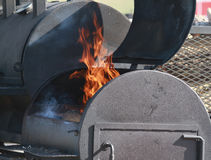 Large BBQ smoker with flames. Huge barbecue meat smoker with flames and door open Royalty Free Stock Images
