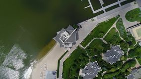 A large beautiful building on the shore of the lake, a view from the drone Large white building on the lake beautiful. Landscape stock footage