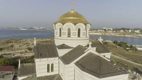 A large beautiful church on the bank of a river near the city. Shot. Fascinating riverside aerial view of the church stock photo