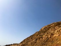 A large beautiful majestic stone sandy mountain, a mound in the desert against a blue sky. Landscape.  Royalty Free Stock Photography