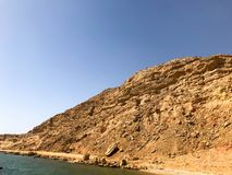 A large beautiful majestic stone sandy mountain, a mound, a hill, a hill in the desert against the blue sky and the sea. Landscape.  Royalty Free Stock Photo