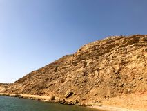 A large beautiful majestic stone sandy mountain, a mound, a hill, a hill in the desert against a blue sky and a salt blue water an. D sea. Landscape Royalty Free Stock Photography