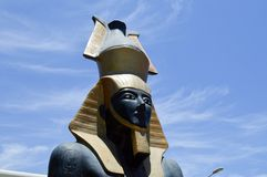 Large beautiful stone statue of a black proud majestic pharaoh in a golden cap, a crown in the shape of a jug against a blue sky stock photography
