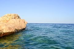 Large beautiful yellow sandy rock, a stone block immersed in saltwater sea blue water against the sky. stock images