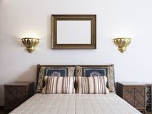 The large bed in the bedroom is middle eastern arabic style with. Patterned pillows and bedspread. The picture above the headboard. 3D rendering stock illustration