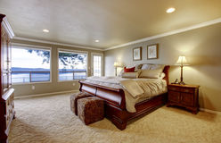 Large bedroom with wood bed and water view. Stock Photography