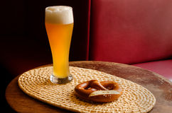 Large beer glass and a pretzel on a woven serving tray in a pub. Large glass of cold beer with pretzel served on woven bamboo tray on an old table in a pub Stock Photography