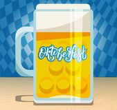 A large beer mug with hand drawn lettering Oktoberfest on the glass side. Flat illustration with foamy pint on wooden table on stock illustration